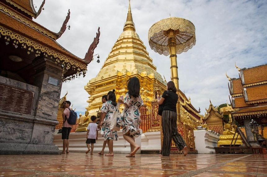 Tourists walking through Wat Phra That Doi Suthep in Chiang Mai, Thailand. where the Buddhist Lent Day is celebrated, marks the official start of the rainy season.