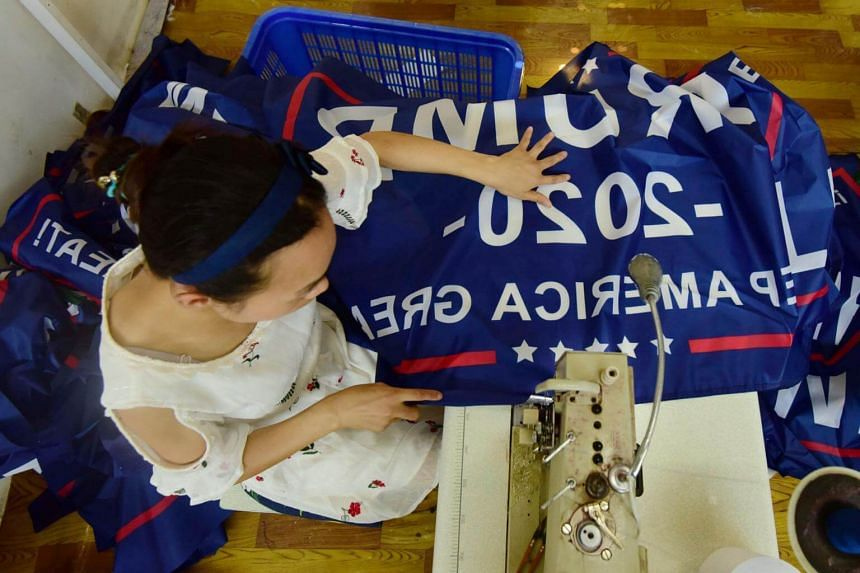 """A Chinese employee sewing a banner declaring US President Donald Trump's re-election intentions as it reads """"Trump 2020: Keep America Great"""" at a factory in eastern Anhui province, China, on July 13, 2018."""