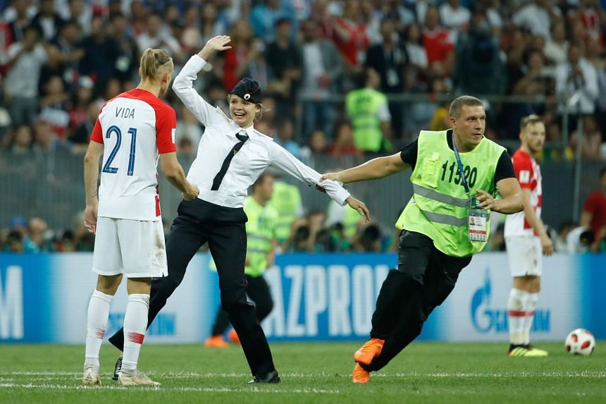 Stewards removing pitch invaders during the Russia 2018 World Cup final football match between France and Croatia at the Luzhniki Stadium in Moscow on July 15, 2018.