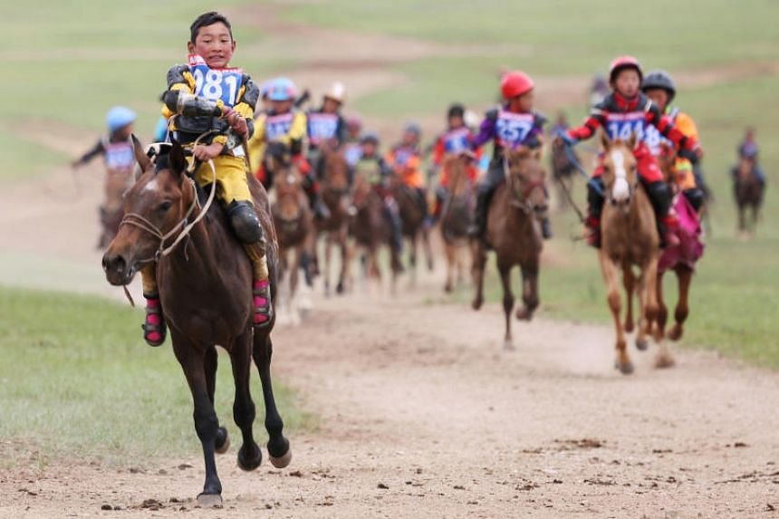 Child jockeys ride their horses to the finish line during a horse race at the Mongolian traditional Naadam festival, on the outskirts of Ulaanbaatar, Mongolia on Jul 12, 2018. PHOTO:REUTERS
