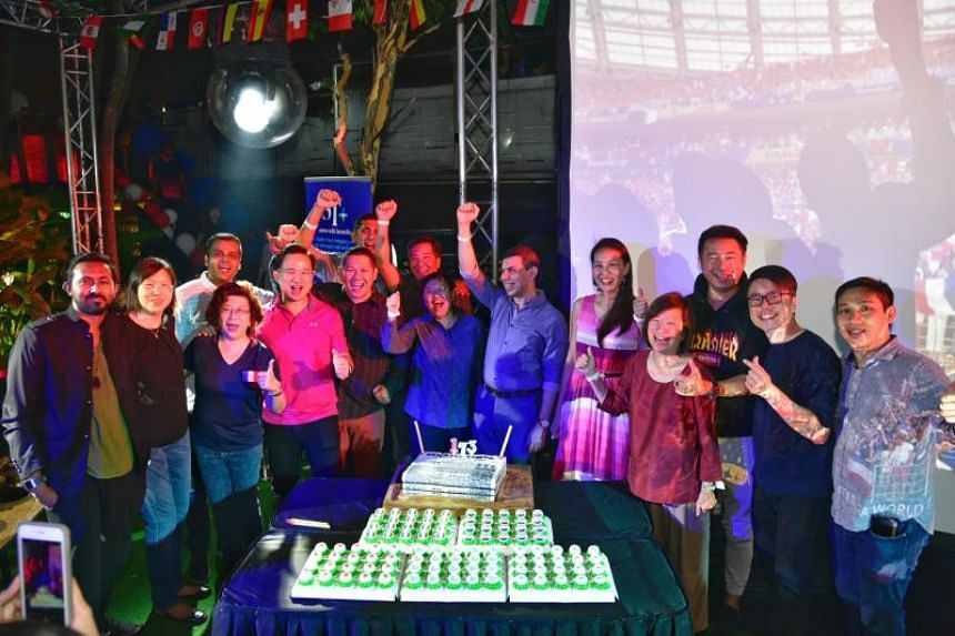ST editor Warren Fernandez (6th from right), ST sports editor Lee Yulin (7th from right), ST news editor Marc Lim (directly behind Yulin) and vice- president of EMTM Irene Ngoo (4th from right), along with ST's invited guests at the ST party and Worl