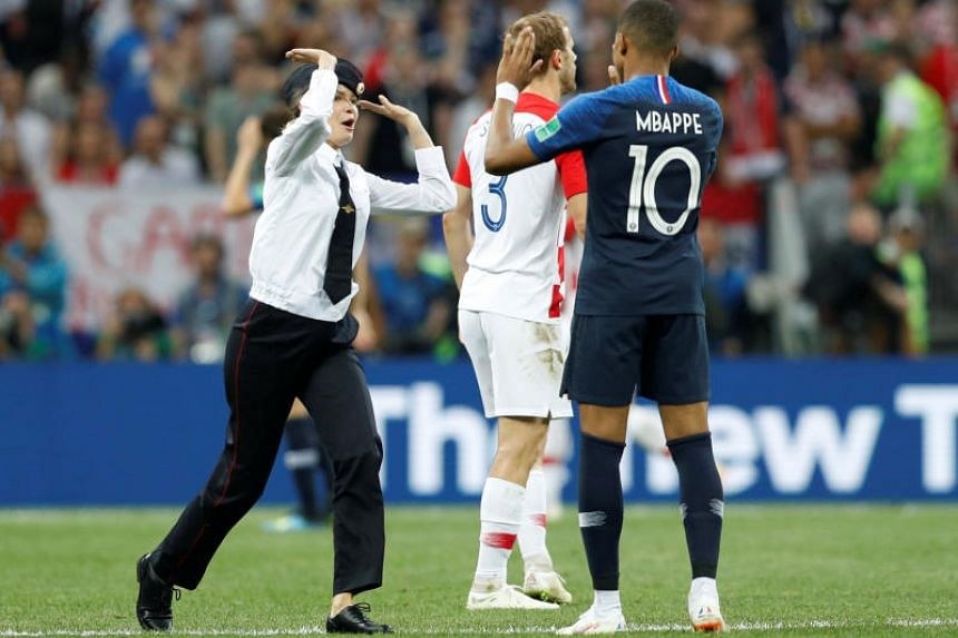 A pitch invader and France's Kylian Mbappe high-five at the Luzhniki Stadium, Moscow, Russia, on July 15, 2018.