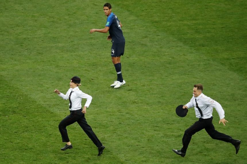 c28d83508 Pitch invaders run on the pitch during the match as France s Raphael Varane  looks on at