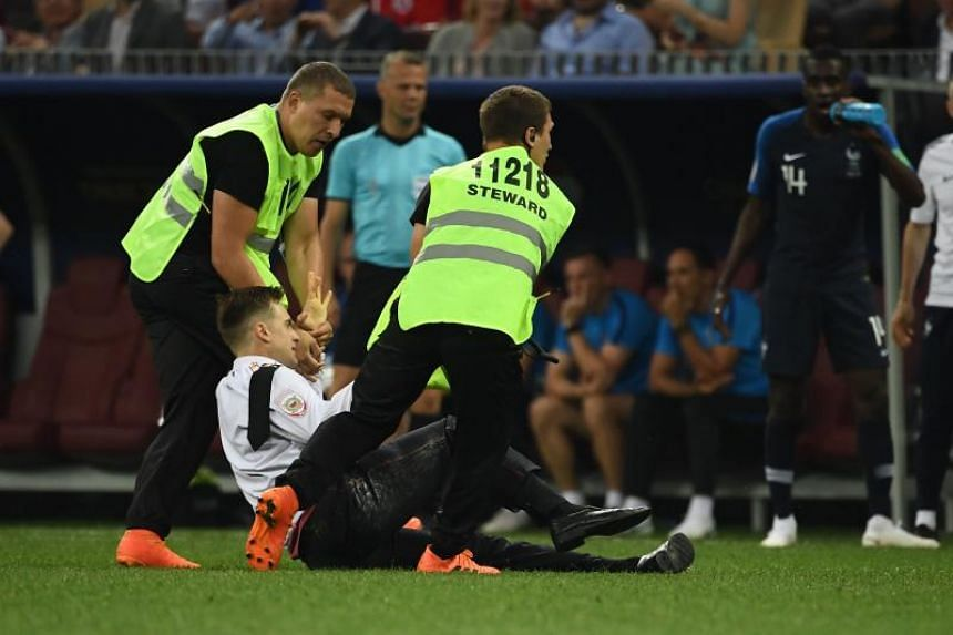 A fan is taken off the pitch during the Russia 2018 World Cup final football match between France and Croatia at the Luzhniki Stadium in Moscow on July 15, 2018.