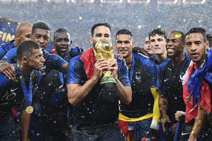 France's defender Adil Rami (centre) kisses their World Cup trophy at the end of the Russia 2018 World Cup final football match between France and Croatia at the Luzhniki Stadium in Moscow, on July 15, 2018.
