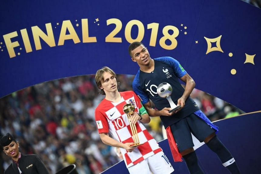 France's forward Kylian Mbappe (right) with his Fifa Young Player award stands beside Croatia's midfielder Luka Modric holding the Adidas Golden Ball prize during the trophy ceremony at the Luzhniki Stadium in Moscow on July 15, 2018.
