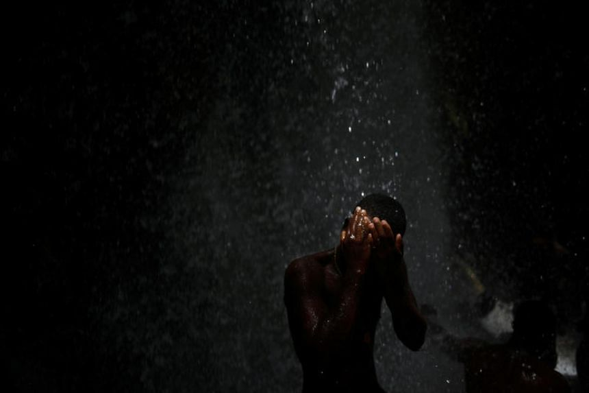 A pilgrim takes a bath during the celebration of the annual pilgrimage to the waterfall in Saut D'Eau, Haiti on Jul 15, 2018. PHOTO:REUTERS