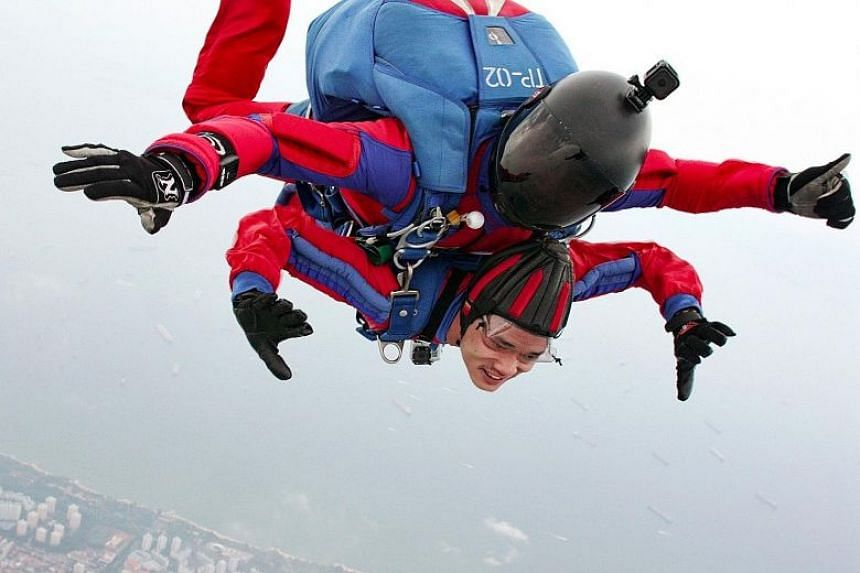 The Straits Times photojournalist Mark Cheong (photo) putting nerves aside for a tandem jump with Red Lions First Warrant Officer (1WO) Dave Chong last Monday.