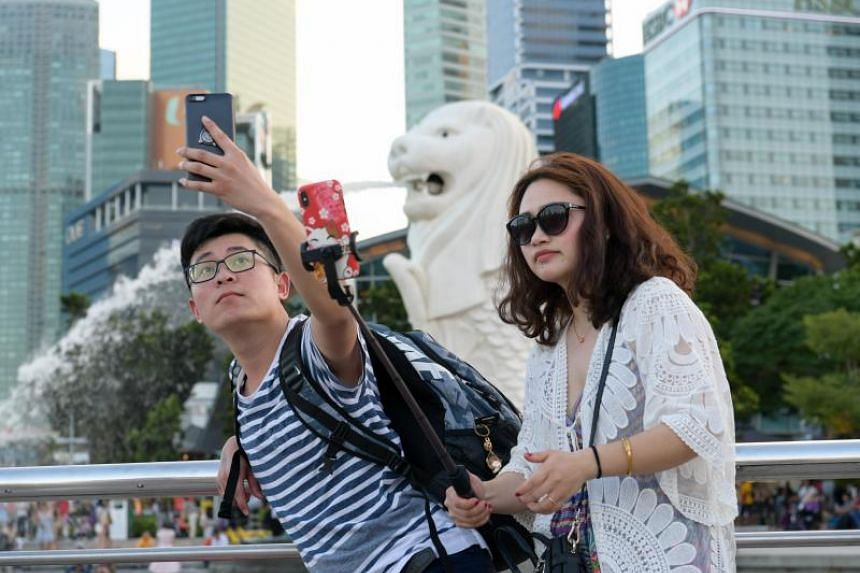Chinese tourists taking pictures in front of the Merlion on Feb 12, 2018.