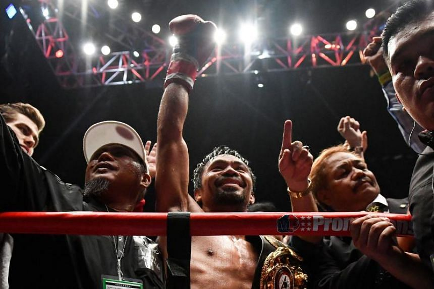Manny Pacquiao (centre) celebrates his victory against Argentina's Lucas Matthysse after their world welterweight boxing championship bout at Axiata Arena in Kuala Lumpur, on July 15, 2018.