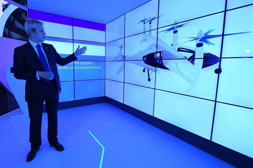 A Rolls-Royce concept flying taxi aircraft is shown in a digital presentation on a screen on the opening day of the Farnborough International Airshow, in Farnborough, Britain, on July 16, 2018.