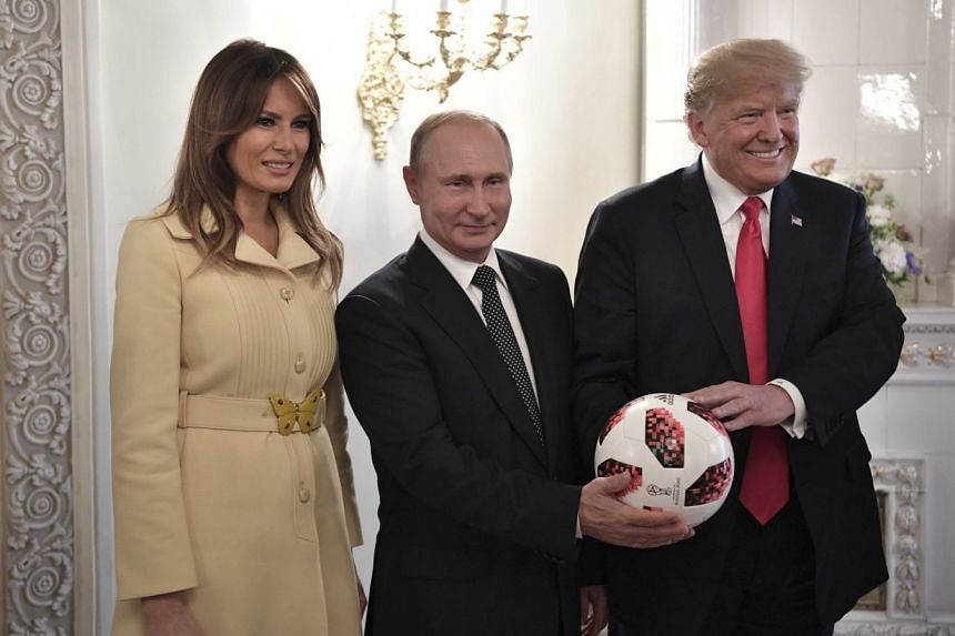Russia's President Vladimir Putin (middle), US President Donald Trump and First lady Melania Trump pose for a picture with a football during a meeting in Helsinki, Finland, on July 16, 2018.