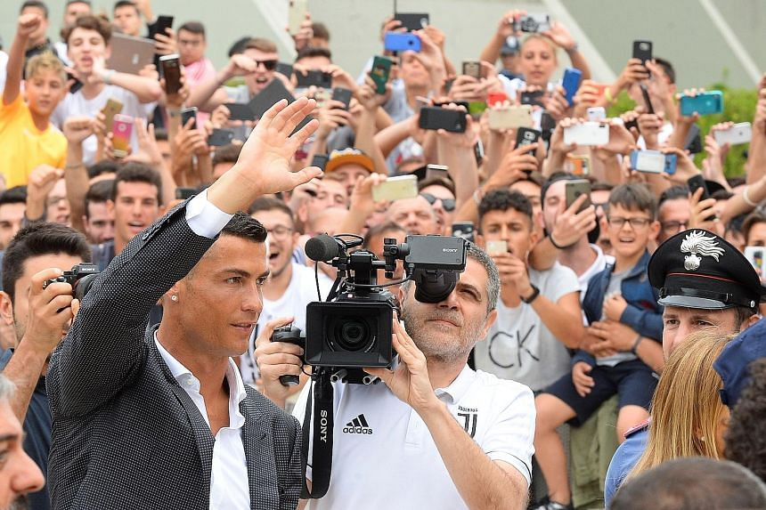 Cristiano Ronaldo waving to Juventus fans as he arrived at the club's medical centre in Turin, Italy yesterday. He will earn a reported €30 million (S$47.9 million) a season.