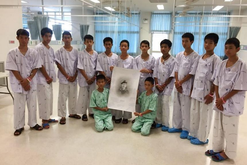 Members of the rescued Wild Boars football team pose after writing messages on a drawing of former Navy SEAL diver Saman Gunan who died on July 6 during the rescue mission.