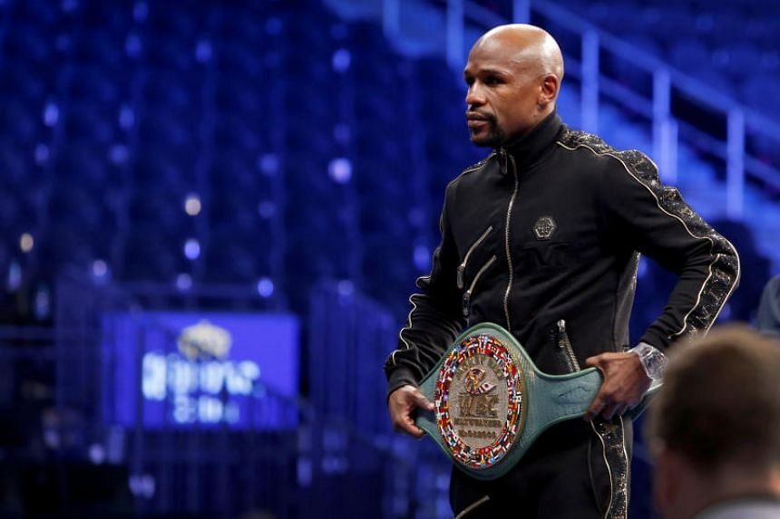 """Undefeated boxer Floyd Mayweather Jr. of the US poses with the WBC """"Money Belt"""" during post-fight news conference at T-Mobile Arena in Las Vegas, Nevada, US, on Aug 27, 2017."""
