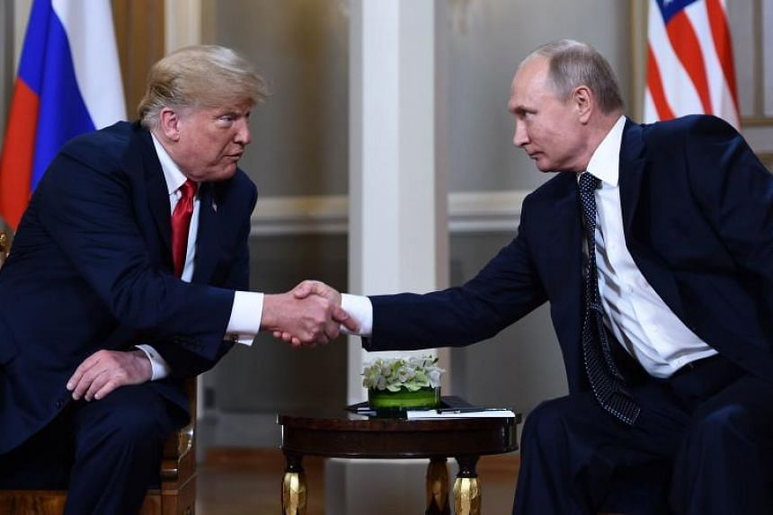 Russian President Vladimir Putin (right) and US President Donald Trump shake hands before a meeting in Helsinki, on July 16, 2018.