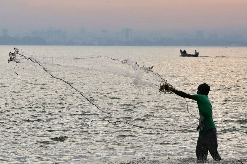 A fisherman casts his net as clouds gather over the Arabian Sea in Kochi, India, on May 26, 2018.