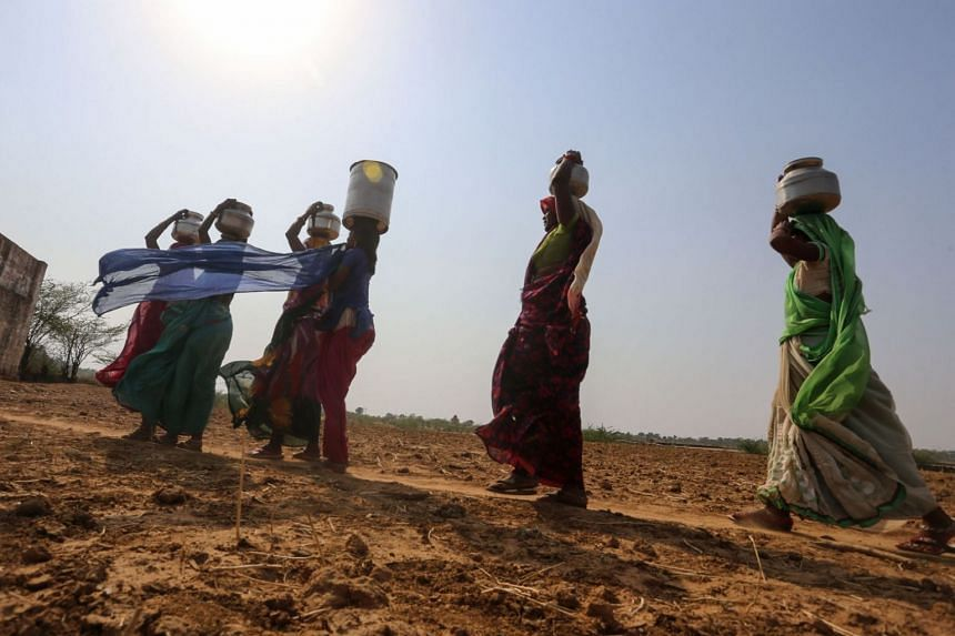 Indian women returning after fetching water from a pit at a lake near Manas Nagar village in Panna district, in the central state of Madhya Pradesh, India.