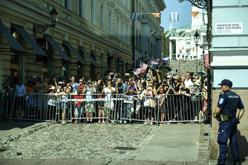 People snapping photos, taking videos and waving flags as President Trump's motorcade passed them in Helsinki yesterday.