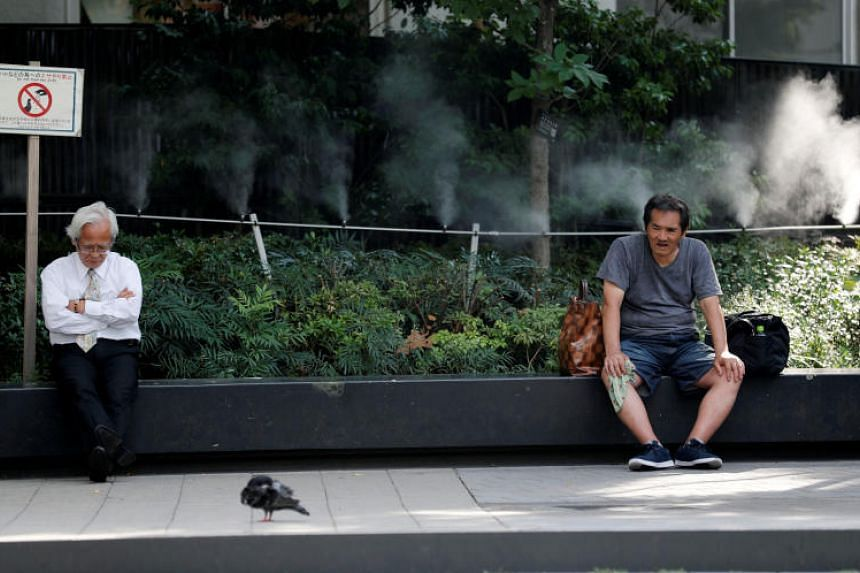 Men take a rest in front of a pipe spraying mist at a park in Tokyo, Japan, on July 17, 2018.