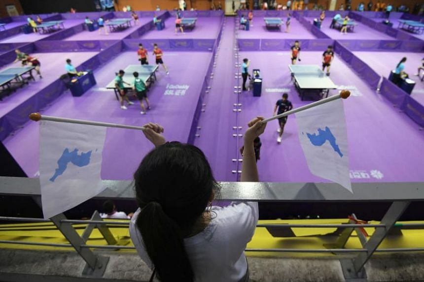 """A South Korean woman holds """"Unification flags"""" as she watches the preliminary round of the International Table Tennis Federation World Tour Platinum Korea Open in Daejeon on July 17, 2018."""