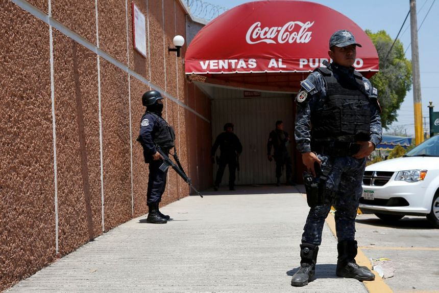 File photo showing police officers guard the entrance of the Coca-Cola FEMSA distribution plant in Guerrero state, Mexico. Masked protesters demanded that the government shut the plant down as clean water became increasingly scarce in April 2017.