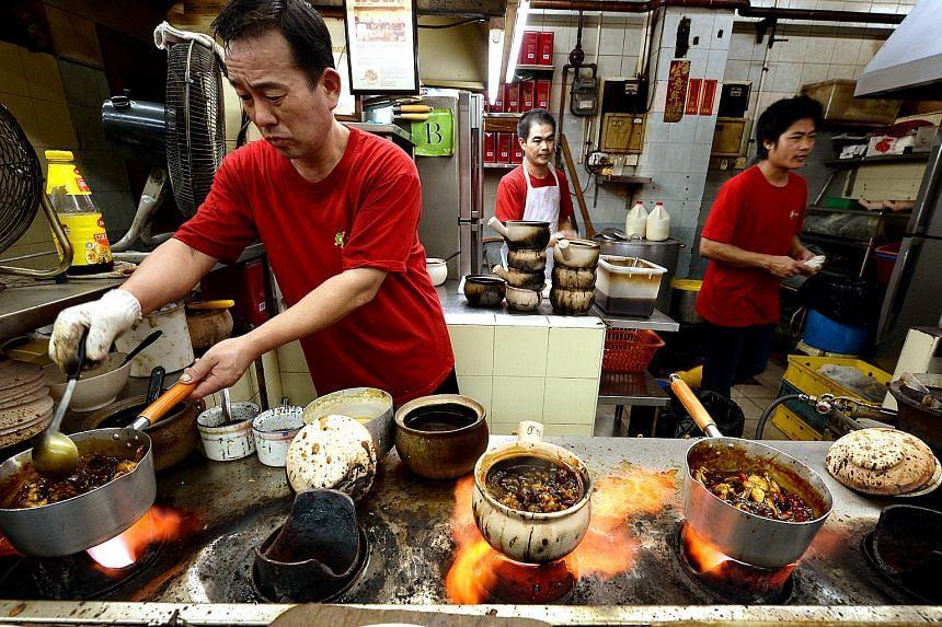 Staff preparing food at Eminent Frog Porridge and seafood, located at Geylang Lorong 19.