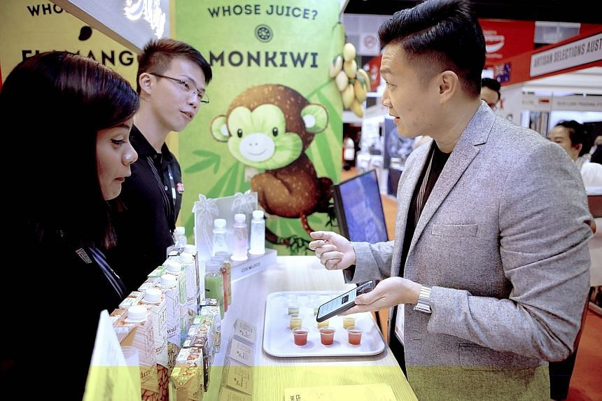 The founder of Whose Juice Kelvin Ngian (right) with his staff Asshah Karim (left) and Elton Liaw. Mr Ngian's company succeeded in producing bottled coconut juice after about a year of trial and error.