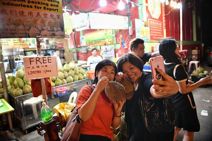 Above: Sam Fruit Trading in Tampines, which had given out free durians on Monday, was swamped by customers. Left: Friends Alice Leung and Gracia Tan with their free durians in Balestier Road.