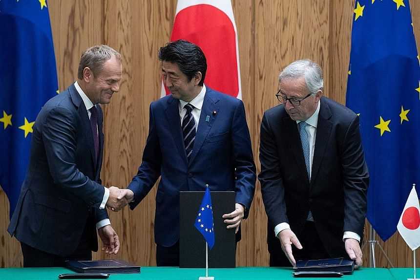 From left: European Council president Donald Tusk, Japan's Prime Minister Shinzo Abe and European Commission president Jean-Claude Juncker after the signing of the free trade deal in Tokyo yesterday.