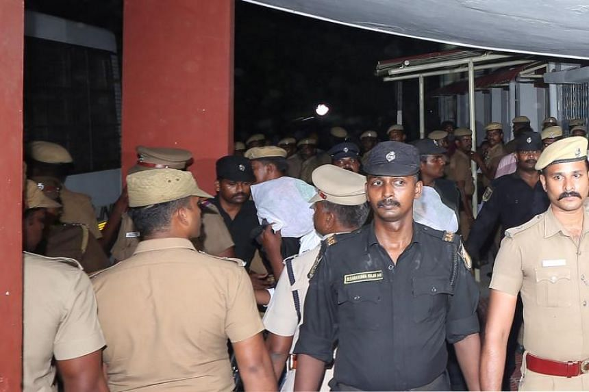 Police escort one of the men (face covered) accused of raping an 11-year-old girl, inside the high court premises in Chennai, India, on July 17, 2018.