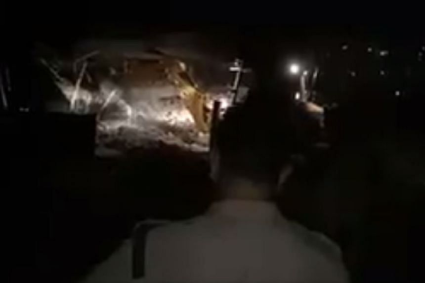 A digger in action at the site of the collapse, in a screenshot from an online news video.