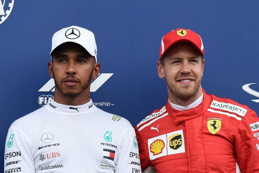 Mercedes' British driver Lewis Hamilton (left) celebrates winning the pole position next to third placed Ferrari's German driver Sebastian Vettel after the qualifying session at the Circuit Paul Ricard in Le Castellet, southern France, on June 23, 20