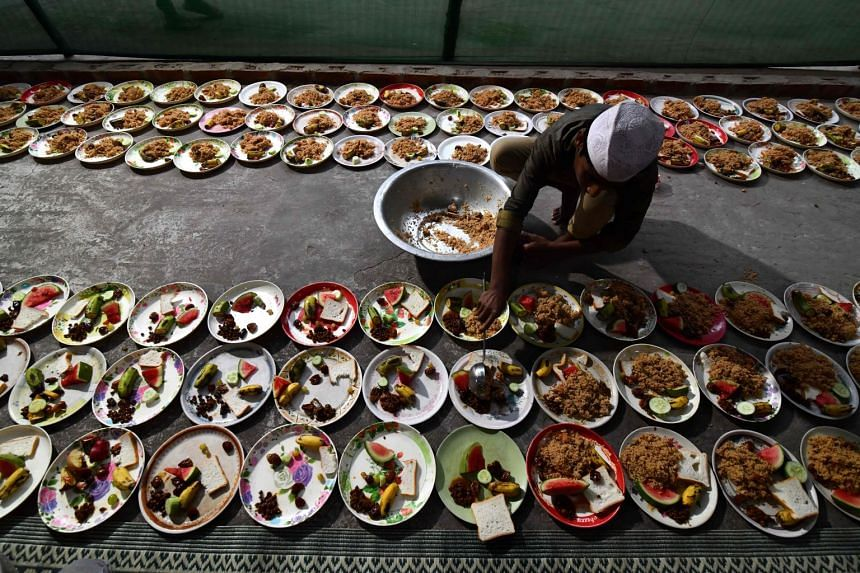 An Indian Muslim man distributing food for Iftar at the Burah Majid in Guwahati city in Assam, on May 17, 2018. With a population of 33 million, Assam is the biggest and fastest-growing among the eight states in north-east India.