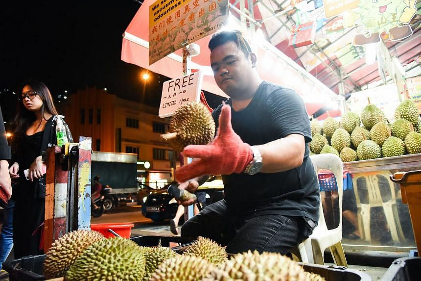 Ah Long, 27, giving out free durian at Ah Soon/Ah Lan durian stall situated at 249 Balestier Road.
