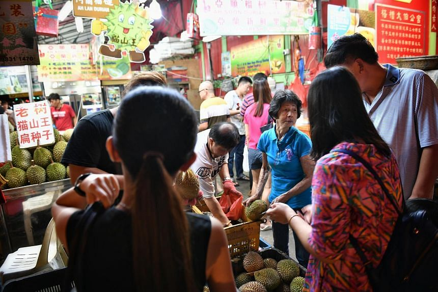 Stall owner Madam Lee Chiew Lan (centre, in blue) giving out free durians at Ah Soon/Ah Lan durian stall, on July 17, 2018.