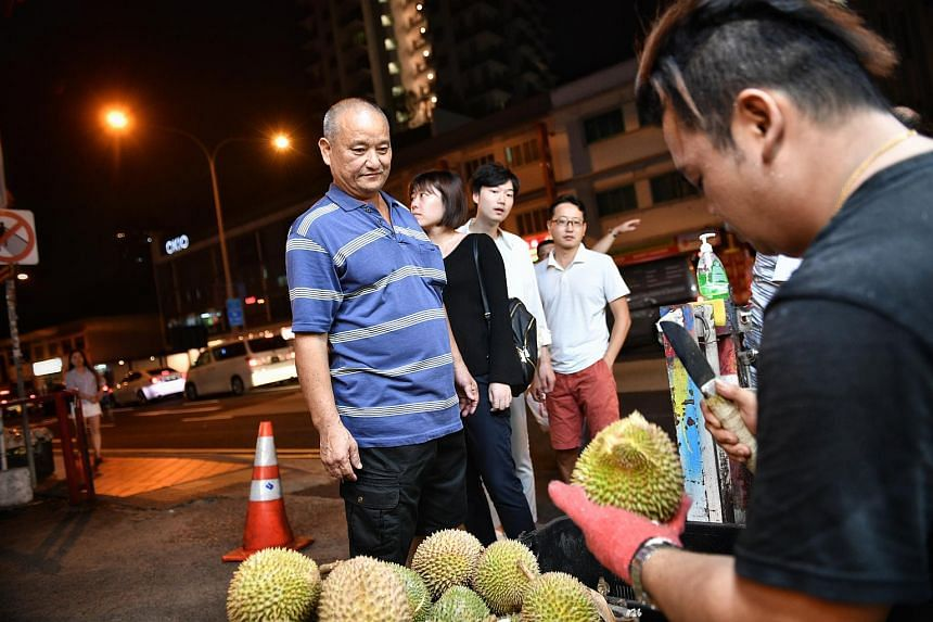 Ah Long opening up the red prawn durians to give to members of the public for free at Ah Soon/Ah Lan durian stall, on July 17, 2018.