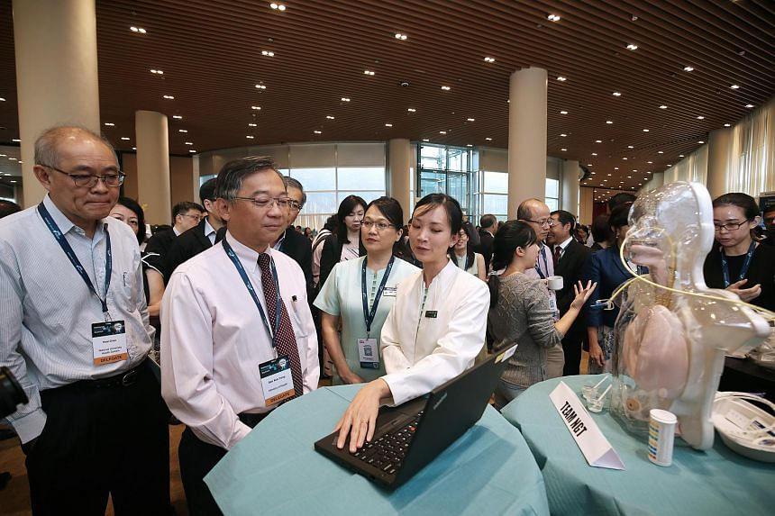 Dr Hossain Nejati (right), a member of the team behind the Stop Lower Extremity Amputations app, explaining the concept of the mobile phone application to Minister of Health Gan Kim Yong (middle) at the National HealthTech Challenge.