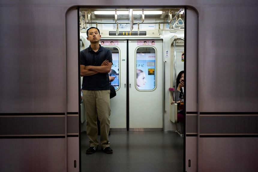 """A man standing inside a subway train in Tokyo. While Tokyo's """"commuter hell"""" has eased since the peak days in the 1960s and 1970s, commuters still have to push their way onto trains on many of the more crowded lines."""