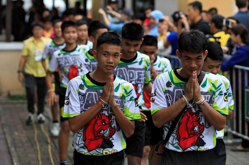 """They also offer traditional """"wai"""" greetings as they arrive for the news conference."""