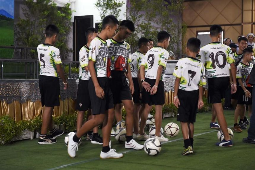 The boys and their coach carry in footballs that they kick gently on the set.