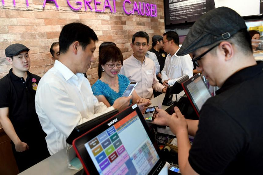 Minister for Education Ong Ye Kung and president of the Autism Resource Centre Denise Phua trying out the Nets Flashpay machine at Professor Brawn in Raffles Institution on July 18, 2018.