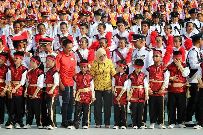 President Halimah Yacob with military tattoo members at a practice session yesterday. There are 220 combined schools choir members this year.