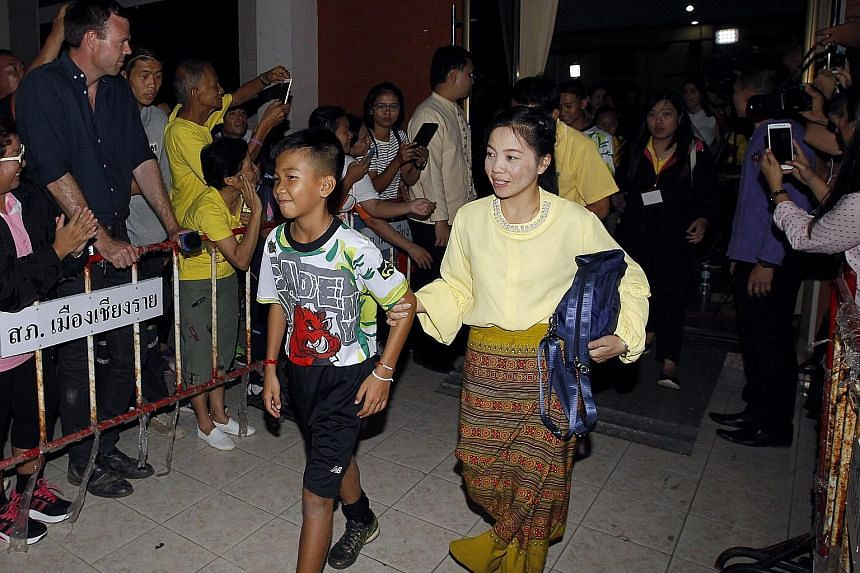 One of the members of the Wild Boars football team being accompanied by his mother as they walk past well-wishers after a media conference in Chiang Rai, Thailand, yesterday. The boys were all dressed in black shorts and T-shirts emblazoned with a re