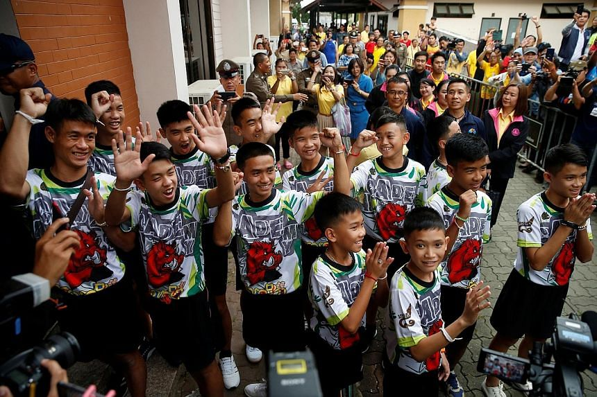Crowds cheering as the 12 football players and their coach arrive for the news conference in the northern Thai province of Chiang Rai yesterday.