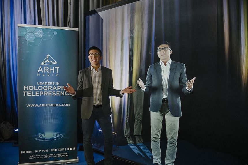 ARHT Media general manager Lincoln Cheung beside a hologram projection of himself. The firm's hologram technology allows speakers and performers to be projected from a distant place using a transparent screen, so that they can engage and interact wit