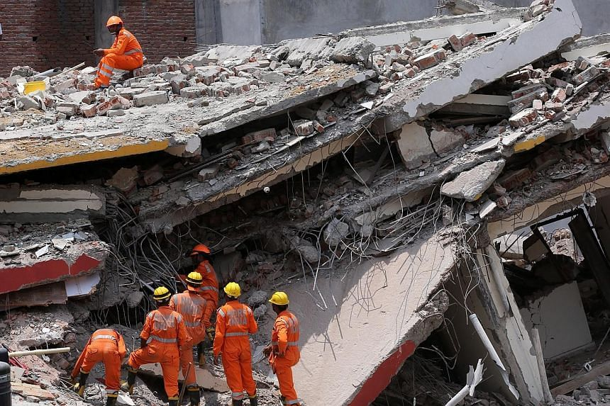 Indian National Disaster Response Force rescue workers clearing rubble yesterday at the site of a building collapse in Greater Noida. It is one of several new areas to have sprung up around New Delhi in the last decade and is home to residential and