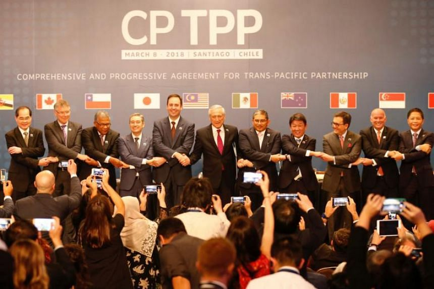 Representatives of members of CPTPP deal, including Singapore's then Minister for Trade and Industry (Trade), Mr Lim Hng Kiang (left), pose for an official picture after the signing agreement ceremony in Santiago, Chile, on March 8, 2018.