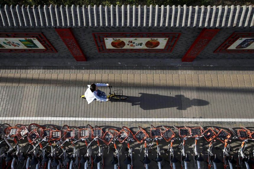 A woman rides an Ofo shared bike past Mobike's shared bikes in Beijing's central business area in China.