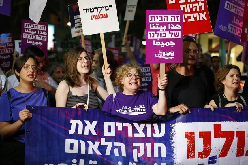 """Demonstrators attend a rally to protest against the Jewish """"nation-state"""" law, in Tel Aviv, on July 14, 2018."""